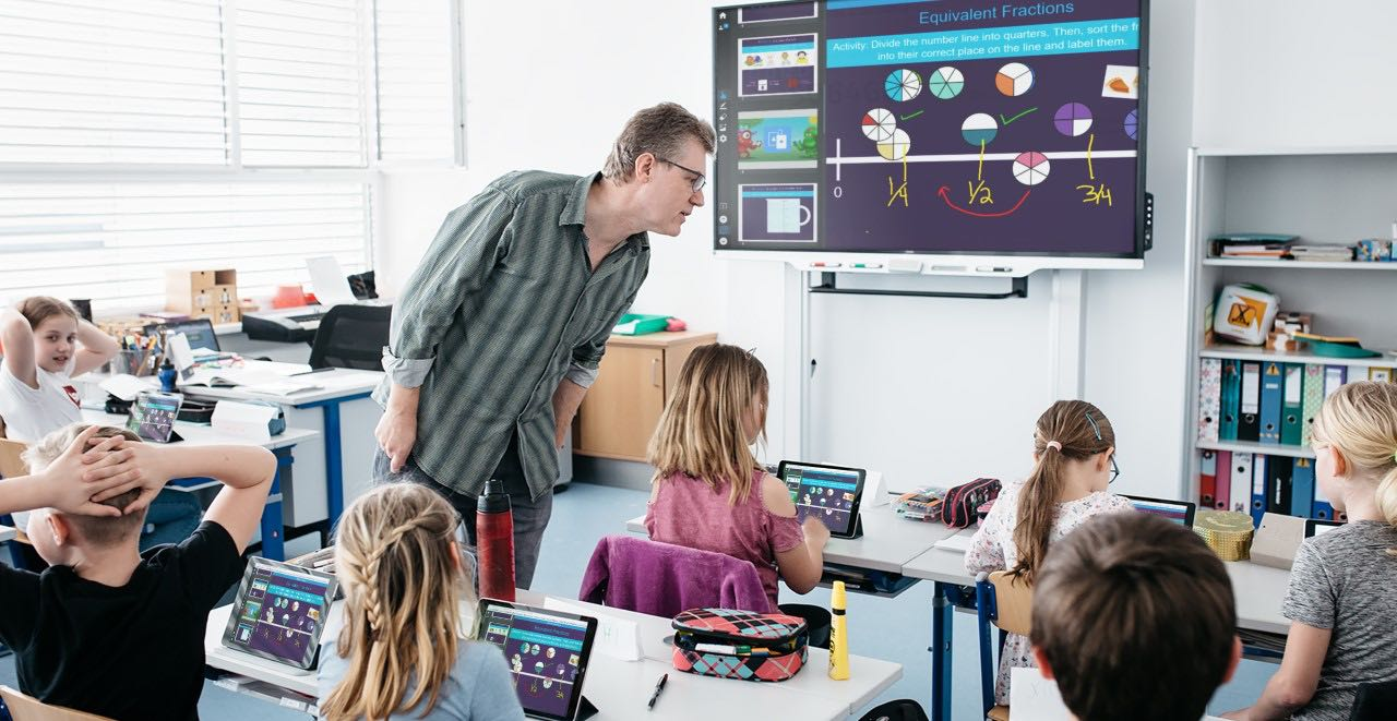 Teacher with SMART Board 7000 series using SMART's Software Learning Suite together with student devices within a classroom.